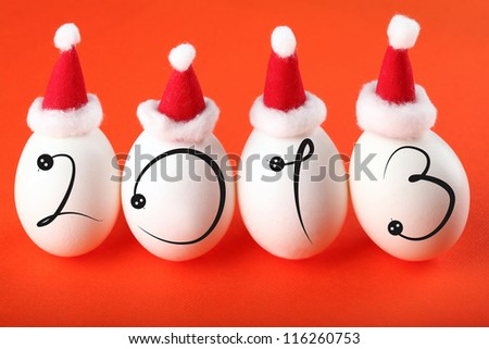 New Year 2013 - Year of black Snake according to Chinese calendar; four eggs in Santa's hats with silhoettes of snakes - stock photo