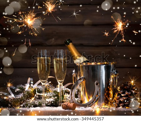 New Years Eve celebration background with pair of flutes and bottle of champagne in  bucket  and a horseshoe as lucky charm - stock photo