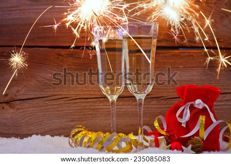new years eve decoration with champagne glasses and fireworks - stock photo