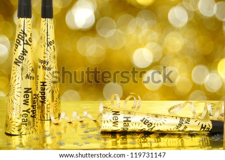 New Years Eve noisemakers and confetti with twinkling gold light background - stock photo