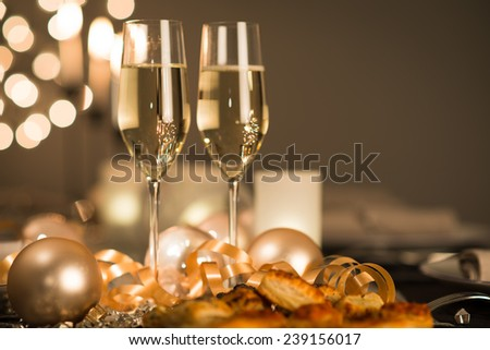 new years eve party table with champagne flute ribbon and golden glitter  - stock photo