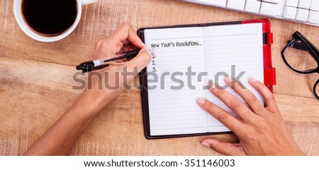 New years resolution list against businesswoman writing on diary on desk - stock photo