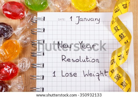 New years resolutions lose weight written in notebook and colorful candies with tape measure, too many sweets, reduction of eating sweets - stock photo