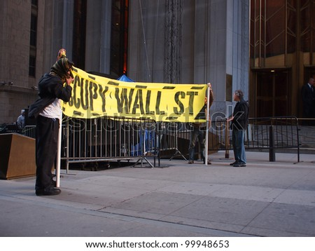 NEW YORK - APR 13: Occupy Wall Street activists hold a banner on Wall Street April 13, 2012 in New York City, NY. Protesters continued their months-long demonstration against the financial system. - stock photo