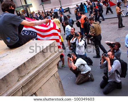 NEW YORK - APR 16: Photographers photograph an unidentified Occupy Wall Street activist holding an upside down American Flag at Federal Hall on Wall Street April 16, 2012 in New York City, NY. - stock photo