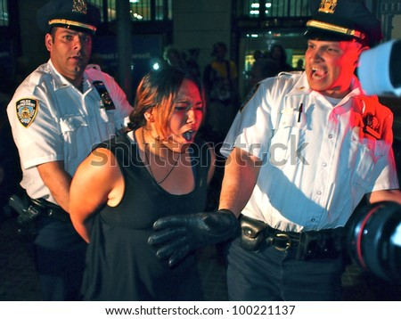 NEW YORK - APR 16: Police arrest an unidentified woman at an Occupy Wall Street rally, April 16, 2012 in New York City. Demonstrators were holding a protest on the steps of Federal Hall. - stock photo