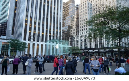 NEW YORK APRIL 5: the crowds is around the Apple Store in Fifth Avenue in New York on 5 april 2012. the store is designed as the exterior glass box above the underground display room - stock photo