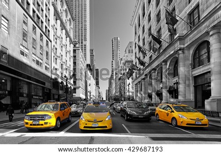 NEW YORK - APRIL 15: Yellow taxis rides on 5th Avenue on April 15 2016 in New York, USA. 5th Avenue is a central road of Manhattan, the most expensive shops and apartmens situated here - stock photo