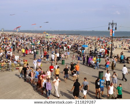 NEW YORK - AUGUST 16: Coney Island boardwalk in Brooklyn, NY on August 16, 2014. Coney Island is about 4 miles long and 0.5 miles wide, and well known as amusement parks and a seaside resort. - stock photo