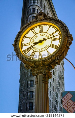 NEW YORK - AUGUST 12:  Fifth Avenue Building clock in front of Flatiron building on August 12, 28th 2012 in New York City at night. The Art Deco clock was installed in 1909. - stock photo