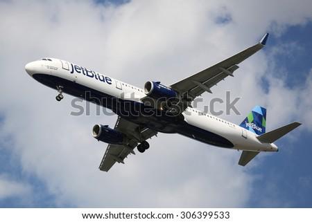 NEW YORK - AUGUST 13, 2015: JetBlue Airbus A321 descending for landing at JFK International Airport in New York - stock photo