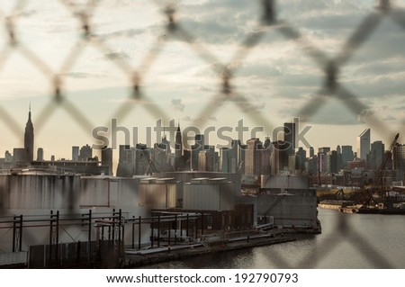 NEW YORK - AUGUST 17: Manhattan through Brooklyn fence on August 17, 2013 in New York. Manhattan is NYC's smallest borough, and contains some of the world's most expensive real estate. - stock photo