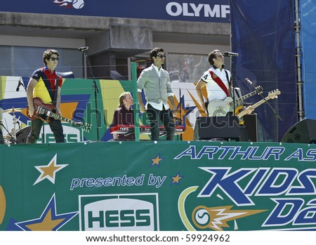 NEW YORK - AUGUST 28: The Jonas Brothers (L-R) Nick, Joe and Kevin perform during the Arthur Ashe Kids Day at US Open August 28, 2010 in New York City - stock photo
