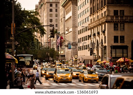 NEW YORK - AUGUST 21: Yellow taxis rides on 5th Avenue on August 21 2012 in New York, USA. 5th Avenue is a central road of Manhattan, the most expensive shops and apartmens situated here - stock photo