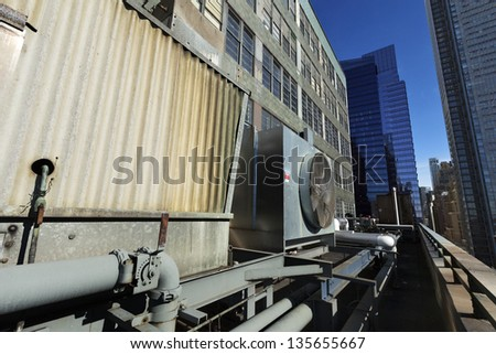 NEW YORK - CIRCA 2011: Wide angle view at an outdoor HVAC air conditioner unit located on a high-floor porch of a midtown Manhattan skyscraper, NY on Circa 2011. - stock photo