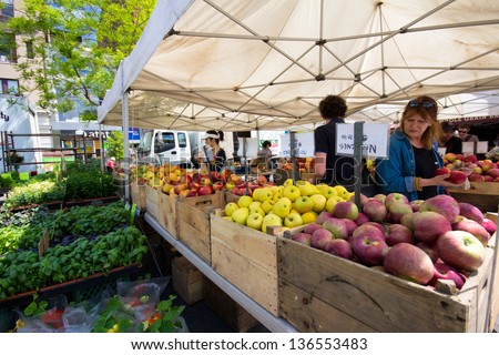 NEW YORK CITY - APR 20: Woman selects produce at Union Square Greenmarket in NYC on Apr 20, 2012. This world famous farmers' market began in 1976 and has grown to 140 farmers during peak season. - stock photo