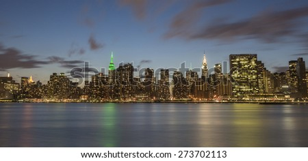NEW YORK CITY - APRIL 22: New York City Manhattan skyline with Empire State Building, Chrysler Building and United Nations building at night over East River on April 22, 2015 in New York City.  - stock photo