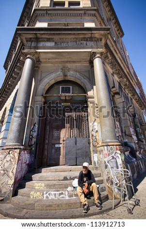 NEW YORK CITY - AUG 30: Man sits on steps of landmark building at 190 Bowery in New York City on Aug. 30, 2012.  This historic building is the Former The Germania Bank Building from the 1890's. - stock photo