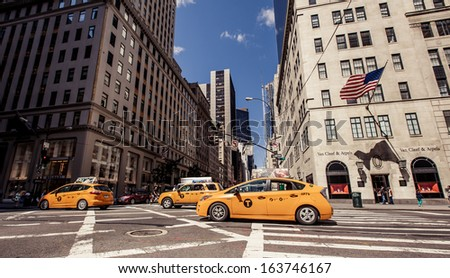 NEW YORK CITY - AUGUST 13: Yellow taxis rides on 5th Avenue on August 13, 2013 in New York, USA. 5th Avenue is a central road of Manhattan, the most expensive shops and apartmens situated here  - stock photo