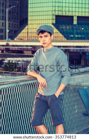 New York City Boy. Wearing newsboy cap, knitting sweater, rolling up pants legs, Asian American college student standing in business district with high buildings, looking at you. Instagram effect.  - stock photo