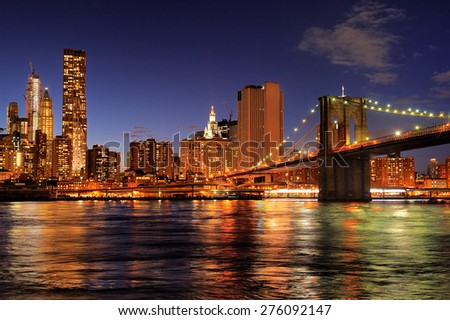 New York City Brooklyn Bridge with downtown skyline over East River at night - stock photo