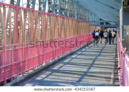 NEW YORK CITY - CIRCA 2015: People run across the Williamsburg Bridge footpath at sunset in New York City 2015. The bridge connects the Lower East Side of Manhattan with Williamsburg in Brooklyn. - stock photo
