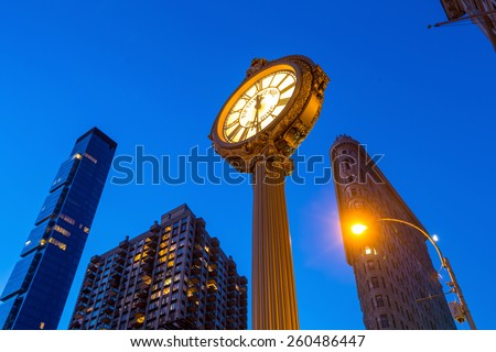NEW YORK CITY - FEB 11: Sidewalk clock and Flat Iron building, considered to be one of the first skyscrapers ever built, with New York City street view. February 11, 2015 in Manhattan, New York City. - stock photo