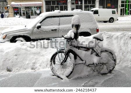 New York City - February 12, 2006:  Delivery bicycles and parked cars on Amsterdam Avenue covered with snow following a winter blizzard - stock photo