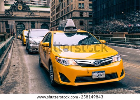 NEW YORK CITY - FEBRUARY 21, 2015:  View of yellow taxi and cars on Park Avenue in midtown Manhattan with Grand Central Terminal in the background.   - stock photo