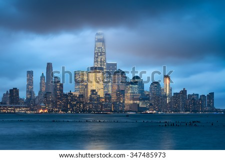 New York City Financial District and illuminated skyline in early evening across Hudson River. Low storm clouds touch the skyscrapers of Lower Manhattan - stock photo