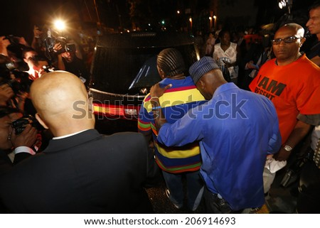 NEW YORK CITY - JULY 23 2014: Funeral services for Eric Garner, the Staten Island resident who died while being taken into custody by NYPD.  Men express grief while standing behind hearse - stock photo