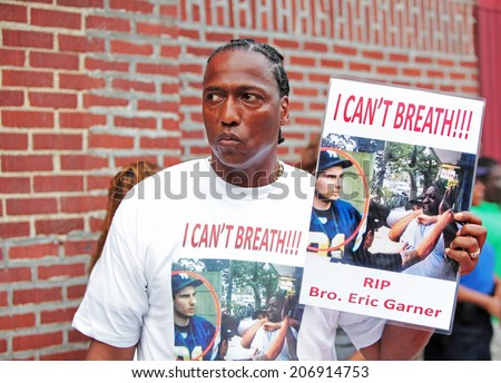 NEW YORK CITY - JULY 23 2014: Funeral services for Eric Garner, the Staten Island resident who died while being taken into custody by NYPD.  Activist with sign. - stock photo