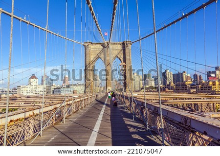 NEW YORK CITY - JULY 9, 2010: Tourists and residents cross Brooklyn Bridge in New York City, New York. Brooklyn Bridge is one of the oldest suspension bridges and was completed in 1883. - stock photo