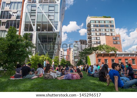 NEW YORK CITY - JUN 15: People walk and relax along the High Line on June 15, 2013. The High Line is a popular linear park built on the elevated train tracks above Tenth Ave in New York City. - stock photo