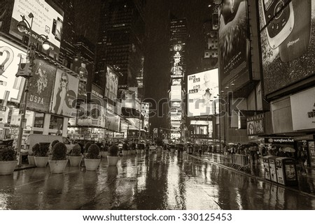 NEW YORK CITY - JUNE 13, 2013: Blurred view of a rainy night scene in Time Square. Times Square is sometimes referred to as The Crossroads of the World. - stock photo