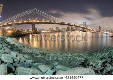 New York City Manhattan Bridge over Hudson River with skyline after sunset night view illuminated with lights viewed from Brooklyn. - stock photo
