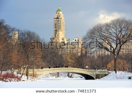 New York City Manhattan Central Park panorama in winter with ice and snow over lake with bridge,  skyscrapers and blue cloudy sky at dusk. - stock photo