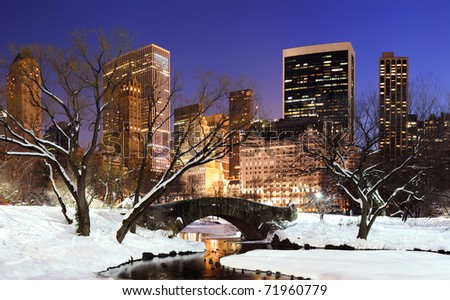 New York City Manhattan Central Park panorama in winter with snow, bridge; freezing lake and skyscrapers at dusk. - stock photo