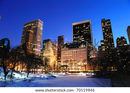 New York City Manhattan Central Park panorama in winter with snow, freezing lake and skyscrapers at dusk. - stock photo