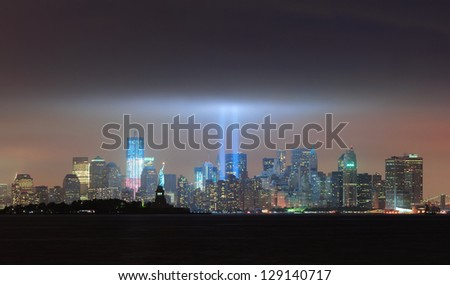 New York City Manhattan downtown skyline panorama at night with statue of liberty and light beams in memory of September 11 viewed from New Jersey waterfront. - stock photo