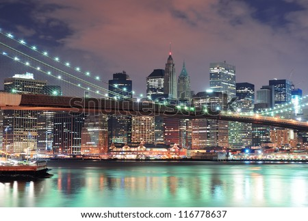 New York City Manhattan downtown skyline with skyscraper and water reflection over East River at night - stock photo