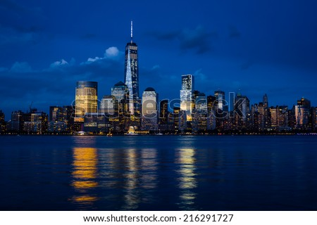 New York City Manhattan downtown skyline with skyscrapers illuminated over Hudson River panorama, including the One World Trade Center - stock photo