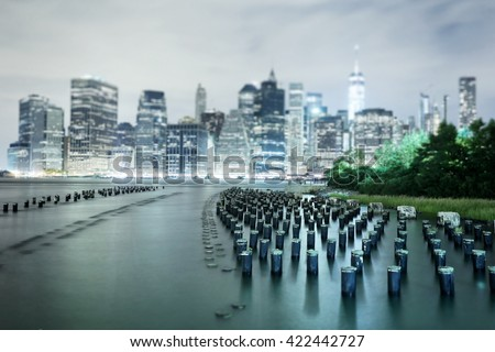 New York City Manhattan downtown skyline with skyscrapers illuminated over Hudson River panorama, including the One World Trade Center. Image with an tilt-shift effect - stock photo