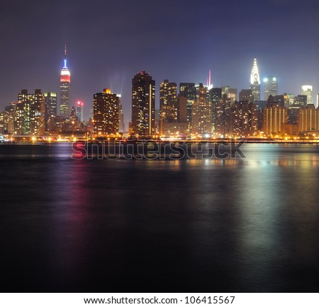New York City Manhattan midtown panorama at night with skyscrapers illuminated over east river - stock photo