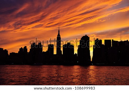 New York City Manhattan midtown silhouette panorama at sunset with skyscrapers and colorful sky over east river - stock photo