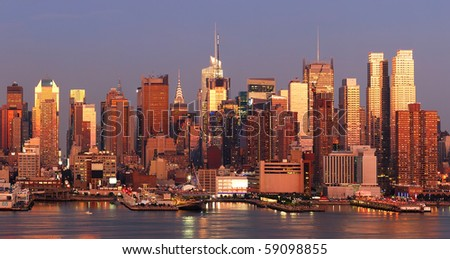 New York City Manhattan skyline panorama at sunset with Times Square and skyscrapers with reflection over Hudson river. - stock photo