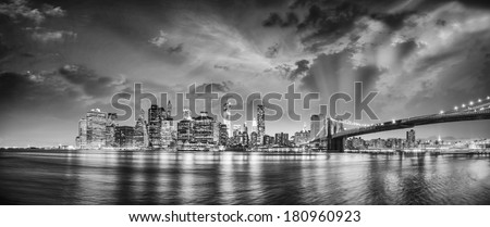 New York City Manhattan skyline panorama with Brooklyn Bridge and office skyscrapers buildings at dusk illuminated with lights at night. - stock photo