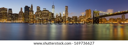 New York City Manhattan skyline panorama with Brooklyn Bridge and office skyscrapers  illuminated with lights at dusk - stock photo