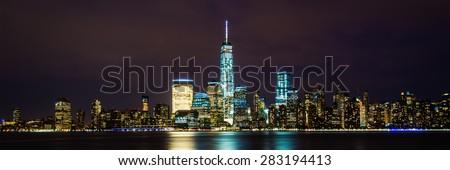 New York City Manhattan skyline panoramic image over Hudson River viewed from New Jersey at night. - stock photo