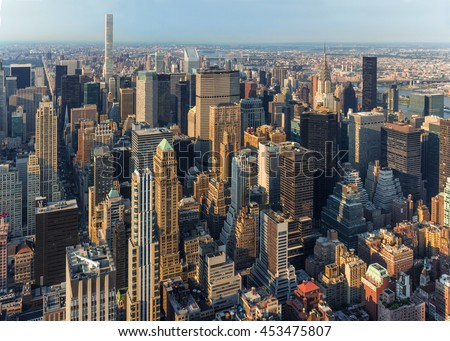New York City Manhattan street aerial view with skyscrapers, pedestrian and busy traffic. Sun at sunset. - stock photo